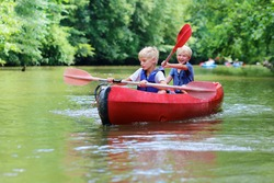 Active happy twin brothers, teenage school boys, having fun together enjoying adventurous experience kayaking on the river on a sunny day during summer vacation