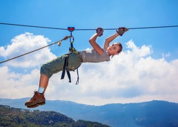 Active happy woman overhanging on tightrope in the mountains on blue sky background, climbing sport, mountaineering adventure, summer trekking concept