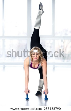 Active, healthy lifestyle, hobby, recreation, wellbeing, weight loss concepts. Sporty dancer girl doing stretching exercises for flexibility and balance with dumbbells, warming up