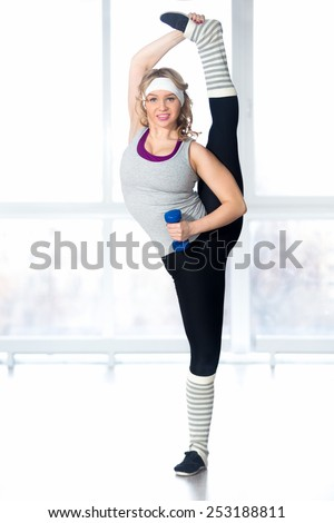 Active, healthy lifestyle, hobby, recreation, wellbeing, weight loss concepts. Sporty sexy dancer girl standing stretching her legs in splits, warming up, enjoying training