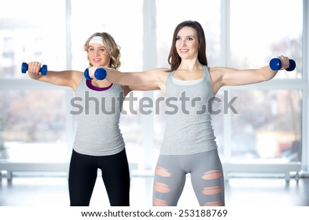 Active, healthy lifestyle, hobby, recreation, wellbeing, weight loss concepts. Team of two athletic girls having intensive aerobics and muscle training with dumbbells in class