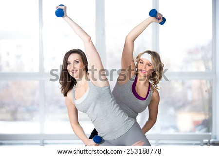Active, healthy lifestyle, hobby, recreation, wellbeing, weight loss concepts. Two athletic girls doing aerobics and muscle training with dumbbells in class