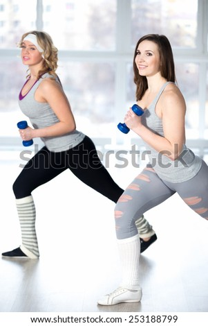 Active, healthy lifestyle, hobby, recreation, wellbeing, weight loss concepts. Two athletic girls doing fitness aerobic exercises with dumbbells in class