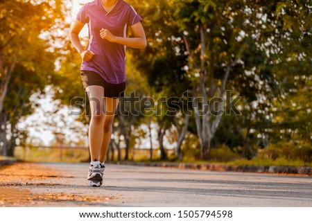 Active healthy runner jogging outdoor. Woman jogging at park in sunrise light