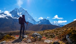 Active hiker hiking, enjoying the view  at Himalaya mountains and Mount Ama Dablam landscape. Travel sport lifestyle concept