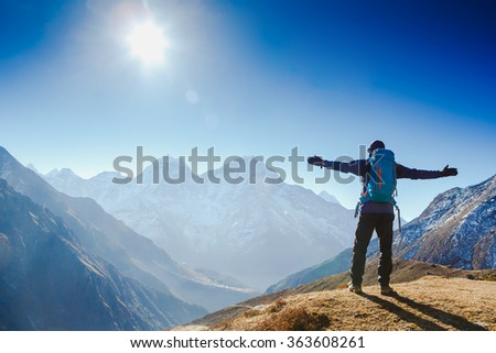 Active hiker hiking, enjoying the view, looking at Himalaya mountains landscape. mountaineering sport lifestyle concept