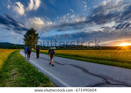 Active hikers hiking on the road with beautiful sunset and dramatic cloudscape #671490604