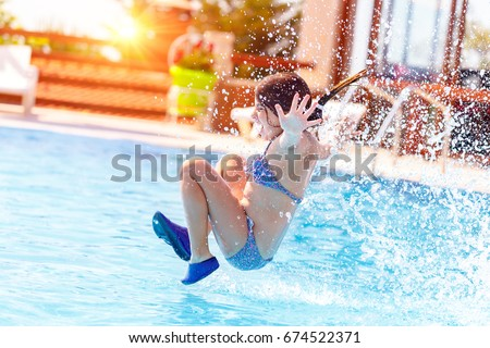Active joyful little girl jumping to the water, having fun in the swimming pool on the beach resort, happy summer holidays