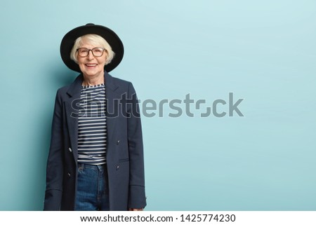 Active joyful stylish female teacher retires, wears hat and formal jacket, glad receiving congratulation from colleagues, has charming smile on face, isolated on blue wall, copy space area for advert