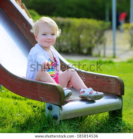 Active kid, adorable blonde toddler girl relaxing on the playground on a sunny summer day sitting on the slide