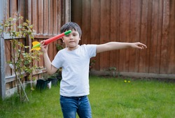 Active kid preparing to throwing a Javelin, Healhty Child practicing athletics throw Javelin. Outdoor activity for Children on Spring or Summer