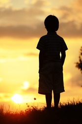 Active kid spending time on summer meadow by sunset