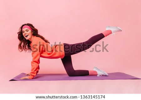 Active lady doing workout for legs on purple fitness mat. Female athlete in pink headband and orange sweatshirt posing on isolated background