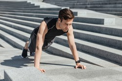 Active leisure and motivation. Millennial guy in sportswear with fitness tracker push up the city stairs at sunlight, free space