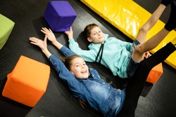 Active leisure. Children having fun on trampoline in entertainment center, childhood and sporty lifestyle. Boy and girl in leisure spotr center for kids. Brother and sister indulge on trampolines.