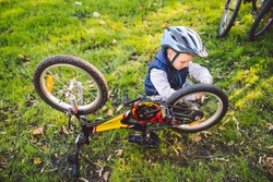 Active leisure for children in the park. A child is studying the mechanism of a mountain bike. Toddler fixing a bike in the forest. Cycling club for children. Little bicycle mechanic at work.