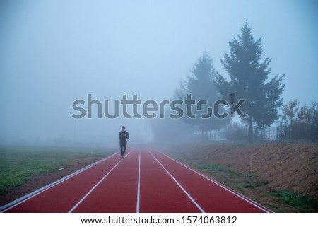Active life, athlete run in misty morning at red athletics or running track