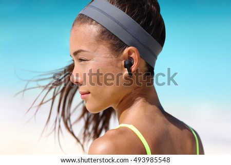 Active life woman listening to music with wireless earbuds. Fitness runner using smartphone phone app on beach wearing earpods on running workout. Asian woman healthy on summer vacation.