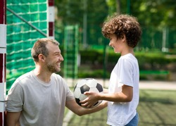 Active Lifestyle Concept. Curly boy holding soccer ball, playing with his dad on stadium, side view