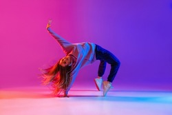Active lifestyle. Dancing as hobby. Young beautiful female hip-hop dancer expresses emotions in dancing isolated on neon background. Concept of dance, youth, hobby, dynamics, movement, action, ad
