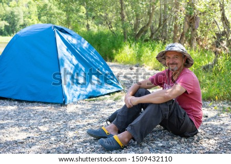 active lifestyle in old age concept, camping, tourism tourism in the elderly grow. an old man in a hat smiles and sits near the tent in the forest #1509432110
