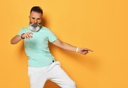 Active lifestyle. Stylish, modern and cool funky trendy gray hipster guy dancing and having fun on a bright orange background. Seniors lifestyle concept. Isolated.
