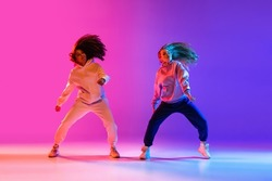 Active lifestyle. Two beautiful hip-hop dancers in motion on gradient pink purple neon background. Sport achievement, expression. Concept of dance, youth, hobby, dynamics, movement, action, ad