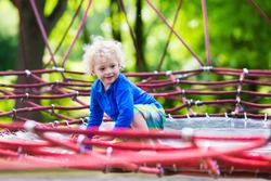 Active little child playing on climbing net and jumping on trampoline at school yard playground. Kids play and climb outdoors on sunny summer day. Funny boy on nest swing at preschool sport center.