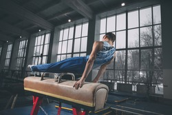 Active. Little male gymnast training in gym, composed and active. Caucasian fit boy, athlete in sportswear practicing in exercises for strength, balance. Movement, action, motion, dynamic concept.