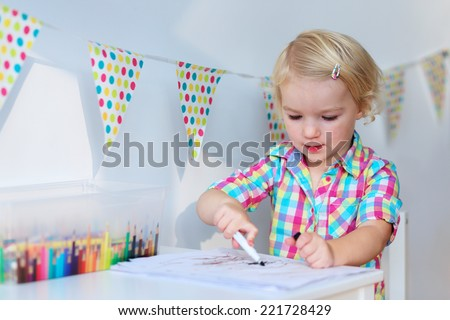 Active little preschool age child, cute toddler girl with blonde curly hair, drawing picture on paper using colorful pencils and felt-tip pens, sitting at white table indoors at home or kindergarten