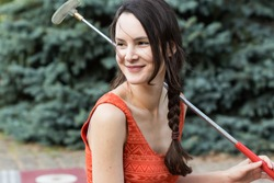 Active living young woman with a golf club