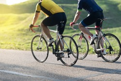 Active male athlete riding bicycles on an open asphalt road. Hills with green grass and the sunset