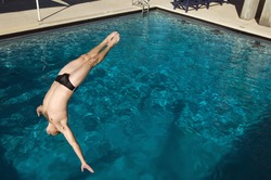 Active male diver diving into the pool