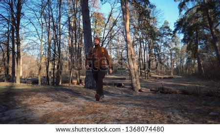 Active male portrait of caucasian sporty man guy hiking outdoors in pine forest. young man tourist with beard and bandage, bandana on his head wearing backpack outdoors goes forward. Wide angle.
