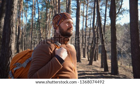 Active male sporty guy portrait hiking outdoors. Young male tourist with a beard and bandage, kerchief on his head wearing a backpack outdoors Caucasian.