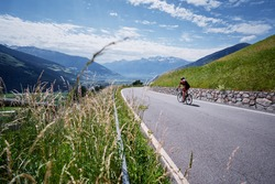 Active male tourist enjoys a scenic bicycle trip along the great alpine route.