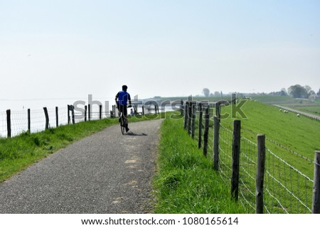 active man bicycling on the dike in Zeeland, Netherlands