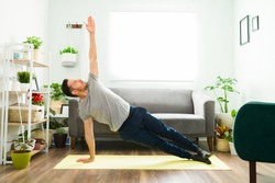 Active man doing a home workout. Fit man in his 30s in a side plank strengthening his body with a yoga routine