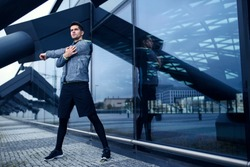 Active man doing his stretching workout next to modern architecture with glass wall. Urban area scenery.