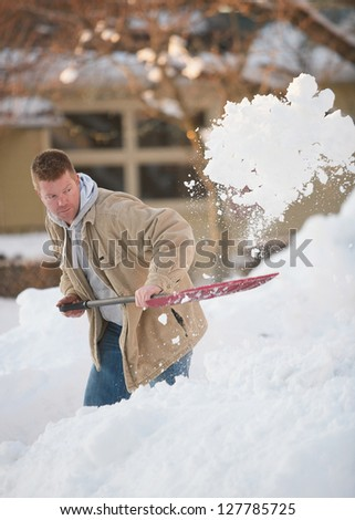 Active man shoveling snow in winter