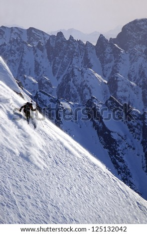 Active man skiing a steep snow slope in Alaska's Chugach Mountains in winter