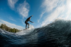 active man skillfully running on the wave with hydrofoil foil board on a background of blue sky and trees