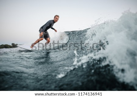 Active man wakesurfing on the board down the blue water against the background of clear sky #1174136941