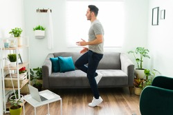 Active man with a healthy lifestyle running in place in the living room. Fit young man doing a high intensity interval training