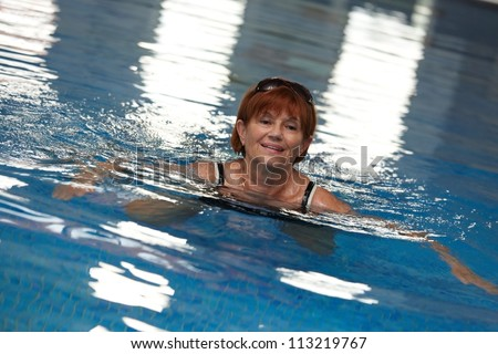 Active mature lady swimming in swimming pool, smiling.