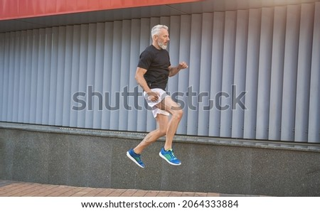 Active middle aged sportive man in sports clothing doing jump exercise while having workout outdoors