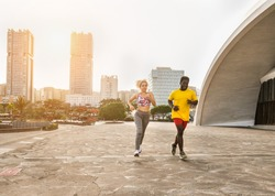 Active multiracial couple running together in the city with sunset - In the background two skyscrapers - Concept of sport activities and healty lifestyle