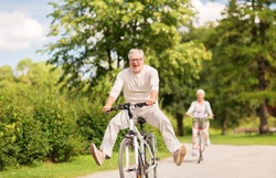 active old age, people and lifestyle concept - happy senior couple riding bicycles at summer park