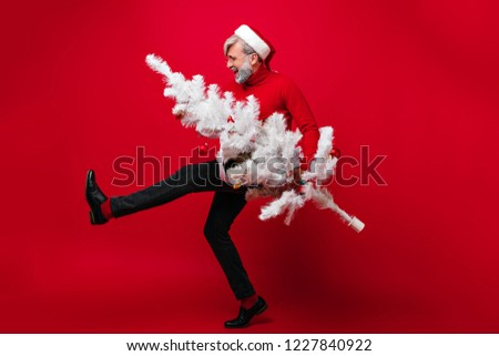 Active old man dancing in new year in studio. Photo of carefree grandpa posing with christmas tree. #1227840922