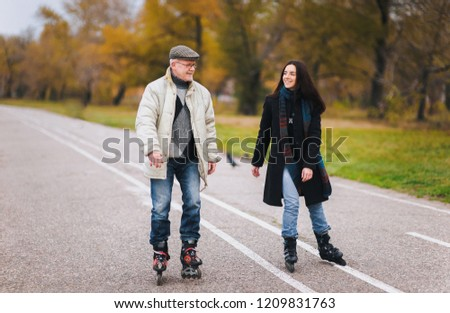 Active old people. The old man goes on rollers with his daughter in the autumn park. Happy pension. Active old people.The old man goes on rollers with his daughter in the autumn park. Happy pension. #1209831763